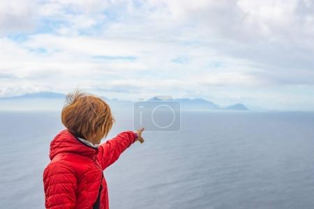 Tourist pointing with finger the rocky coast line at Cape Point, Table Mountain National Park, South Africa. Winter season, cloudy and dramatic sky.