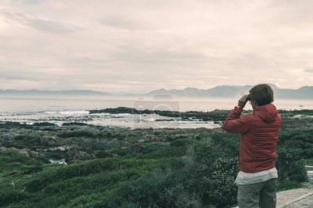 Tourist looking with binocular on the rocky coast line at De Kelders, South Africa, famous for whale watching. Winter season, cloudy and dramatic sky, toned image.