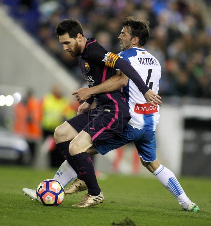 Leo Messi(L) of FC Barcelona fights with Victor Alvarez(R) of RCD Espanyol
