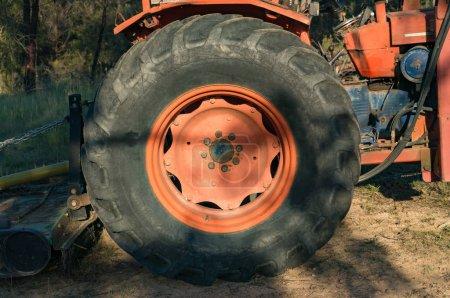 Photo pour Gros plan de la roue du bulldozer avec des pièces métalliques rouges et pneu noir. Construction machinerie lourde détail - image libre de droit