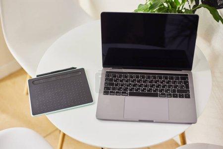 Photo pour Ordinateur portable avec une tablette graphique sur une table dans un café. Lieu de travail indépendant . - image libre de droit