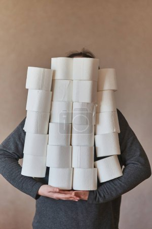 A girl holds many rolls of toilet paper. Quarantin...