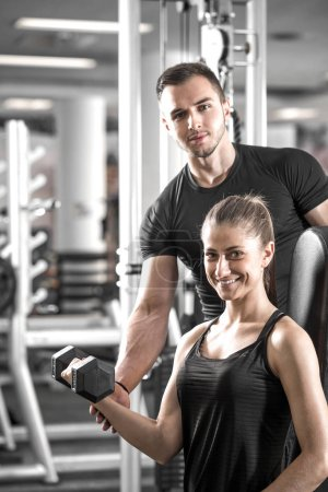 Young adult woman working out in gym, doing bicep curls with help of her personal trainer.