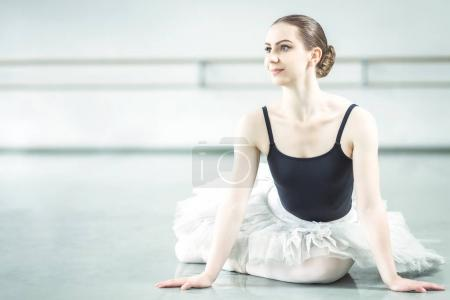 Bellerina sitting on the floor in ballet studio