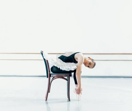 Bellerina sitting on chair in ballet studio
