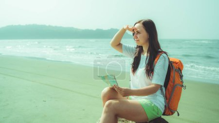Female tourist reading map near sea. Barefoot woman with backpack sitting on driftwood and examining map while resting on sandy beach near waving sea