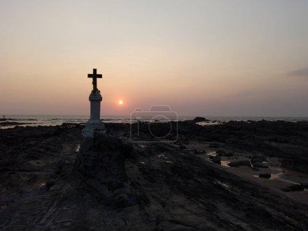 Photo pour La croix chrétienne sur les rochers au bord de la mer contre le coucher du soleil - image libre de droit