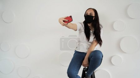 Photo for Young woman in black medical mask taking selfie on smartphone on background of white wall. Portrait of female spending time weekend at home and photographing of herself on mobile phone - Royalty Free Image