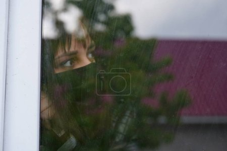 Photo for Portrait of thoughtful female with brown eyes observing through window. - Royalty Free Image