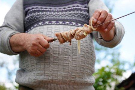 Photo pour L'homme mûr empale du shashlik cru sur une brochette. Gros plan des mains des hommes tiennent une brochette avec barbecue . - image libre de droit