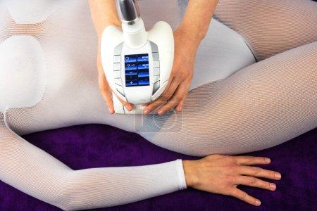 Photo pour Corps féminin en costume blanc spécial ayant massage anti-cellulite avec appareil de spa - image libre de droit