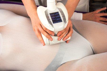 Photo pour Corps de la femme en costume blanc spécial ayant anti cellulite massage avec appareil spa - image libre de droit