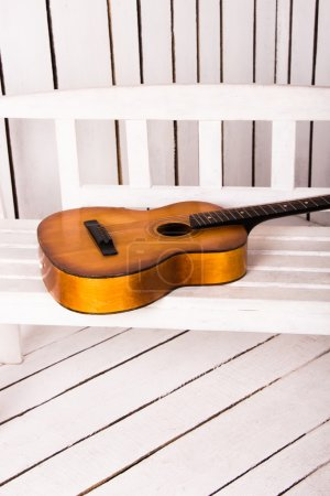 Acoustic guitar with abstract wooden background