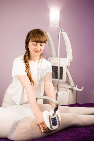 Photo pour Un thérapeute qualifié fait un massage anti-cellulite avec un appareil dans un salon de spa - image libre de droit
