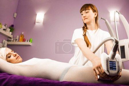 Photo pour Femme ayant anti cellulite massage avec appareil et thérapeute - image libre de droit