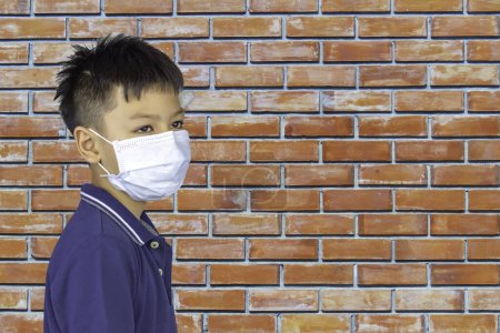 Photo for Portrait  Asian boy wearing a mask background brick wall. - Royalty Free Image