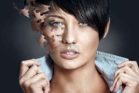 Beautiful woman with jigsaw puzzle pieces of skin. Fashion art portrait. Cosmetics concept