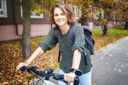 Beautiful young female student in a sweater and jeans on a bicyc