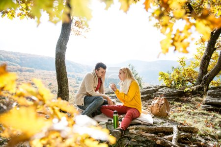 couple in autumn forest eating and drinking