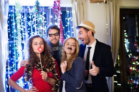 Photo for Beautiful hipster friends with photobooth props celebrating the end of the year, having party on New Years Eve, chain of lights behind them. - Royalty Free Image