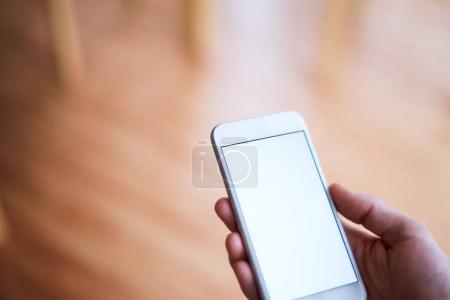 Photo pour Une image de la maquette d'une main tenant le smartphone avec un écran blanc vide. Système intelligent de contrôle domestique. - image libre de droit