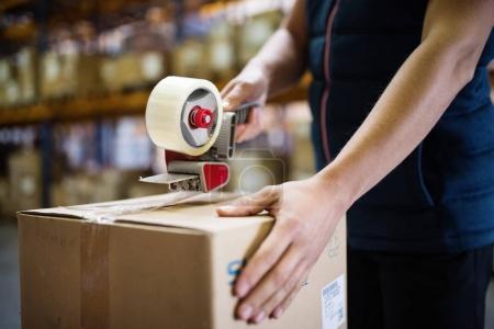 Photo pour Ouvrier d'entrepôt masculin méconnaissable ou boîtes en carton d'étanchéité supercisor . - image libre de droit