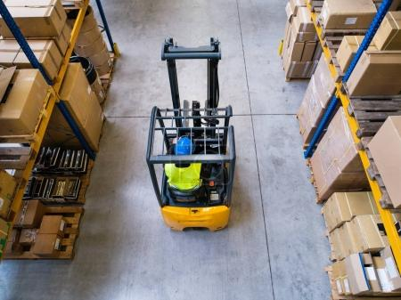 Photo for Man forklift driver working in a warehouse. Aerial view. - Royalty Free Image