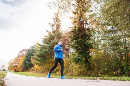 Photo pour Jeune athlète en veste bleue en cours d'exécution à l'extérieur dans la nature automne ensoleillé coloré. Trail runner formation pour traverser le pays en cours d'exécution. - image libre de droit