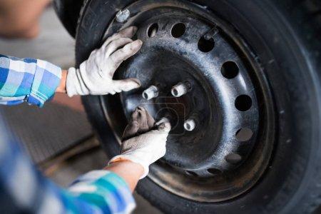 Photo pour Mécanicien féminin réparant une voiture. Une femme méconnaissable travaillant dans un garage . - image libre de droit