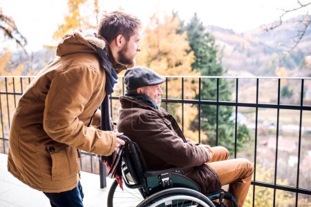 Photo for Father in wheelchair and young son on a walk. A carer assisting disabled senior man. - Royalty Free Image
