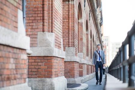 Reifer Geschäftsmann zu Fuß in einer Stadt.