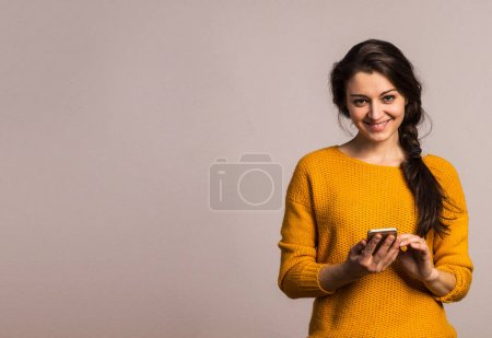 Photo for Studio portrait of a young beautiful woman with smartphone. Copy space. - Royalty Free Image