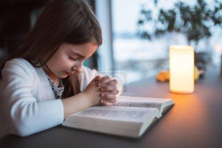 Photo pour Une petite fille avec la bible à la maison, prier. - image libre de droit