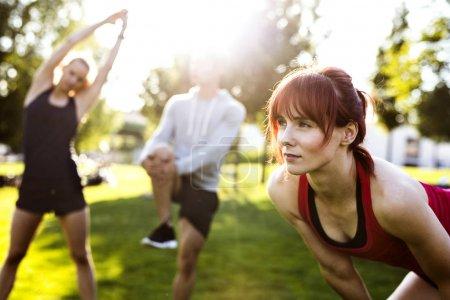 Photo pour Groupe de jeunes coureurs dans la nature échauffer et étirer les bras et les jambes . - image libre de droit
