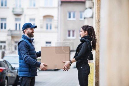 Photo pour Jeune femme recevant un colis du livreur à la porte - concept de service de messagerie . - image libre de droit
