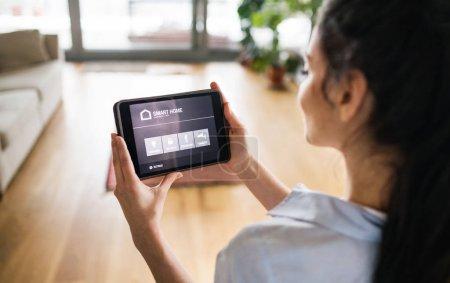 Photo pour Une femme méconnaissable, tenant une tablette avec système de contrôle intelligent de maison. - image libre de droit