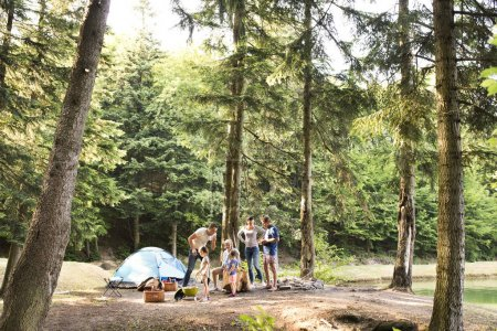 Photo for Beautiful family enjoying camping holiday in forest. - Royalty Free Image