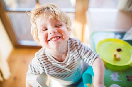 Photo pour Un mignon tout-petit garçon manger à la maison . - image libre de droit