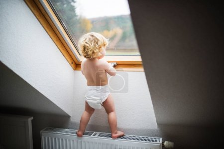 Photo for Little toddler boy standing on a radiator, opening a window. Domestic accident. Dangerous situation at home. Rear view. - Royalty Free Image