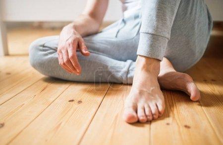 Photo pour Homme pieds nus méconnaissable assis sur le sol dans la chambre à coucher à la maison . - image libre de droit
