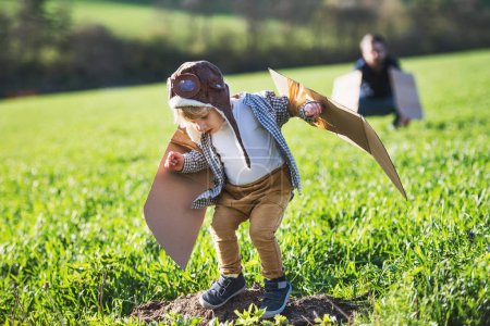 Photo for Happy toddler boy with hat, goggles and wings playing outside with unrecognizable father in spring nature. Pilot and flying concept. - Royalty Free Image