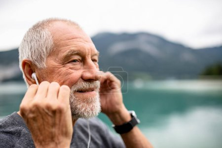 Photo for A senior man with earphones standing by lake in nature, listening to music. - Royalty Free Image