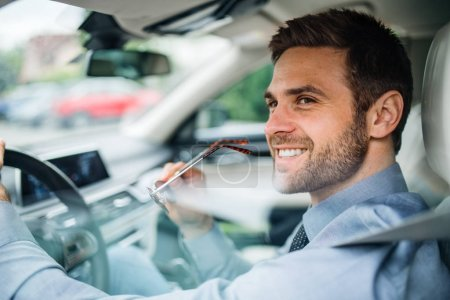 Photo for A young businessman with shirt sitting in car. Shot through glass. - Royalty Free Image