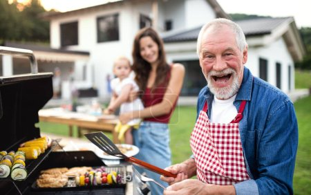 Photo for A portrait of multigeneration family outdoors on garden barbecue, grilling. - Royalty Free Image