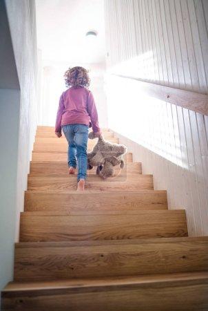 Photo pour Vue arrière d'une petite fille qui monte des escaliers en bois à la maison. Table des matières. - image libre de droit