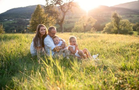 Photo for Happy young family with two small children sitting on meadow outdoors at sunset. - Royalty Free Image
