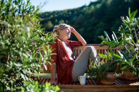 Photo for Side view of senior woman sitting outdoors on terrace, resting. - Royalty Free Image