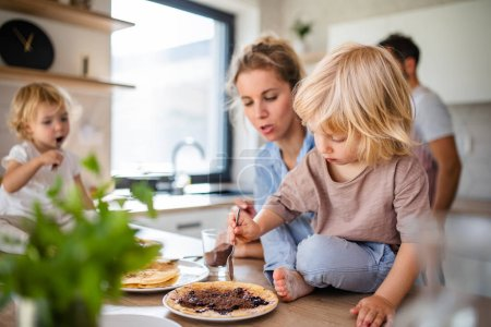 Photo for A young family with two small children indoors in kitchen, eating pancakes. - Royalty Free Image