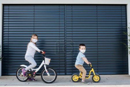 Photo for Small girl and boy with bicycles and face masks outdoors at home. Corona virus and quarantine concept. - Royalty Free Image