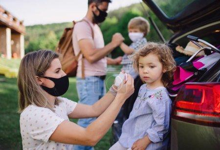 Familia con dos niños pequeños cargando el coche para el viaje en el campo, con máscaras faciales .